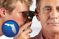 florida an audiologist examining the ear of a patient