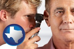 texas an audiologist examining the ear of a patient