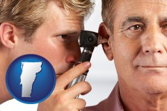 vermont an audiologist examining the ear of a patient