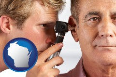 wisconsin an audiologist examining the ear of a patient