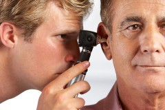 an audiologist examining the ear of a patient