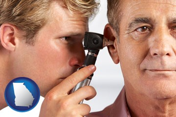 an audiologist examining the ear of a patient - with Georgia icon