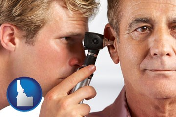 an audiologist examining the ear of a patient - with Idaho icon