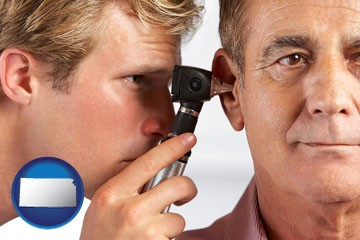 an audiologist examining the ear of a patient - with Kansas icon