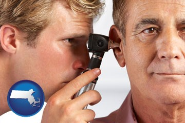 an audiologist examining the ear of a patient - with Massachusetts icon