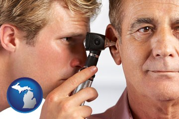 an audiologist examining the ear of a patient - with Michigan icon