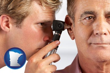 an audiologist examining the ear of a patient - with Minnesota icon