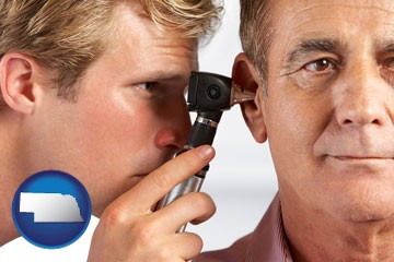 an audiologist examining the ear of a patient - with Nebraska icon