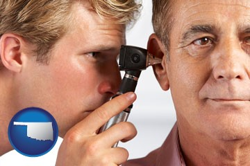 an audiologist examining the ear of a patient - with Oklahoma icon
