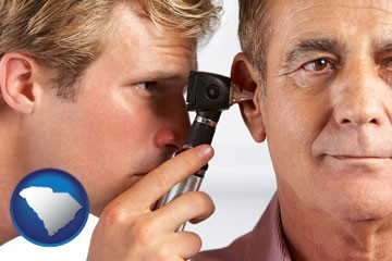 an audiologist examining the ear of a patient - with South Carolina icon