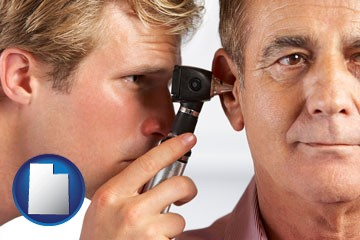 an audiologist examining the ear of a patient - with Utah icon